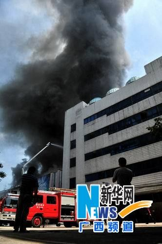 消防人员在广西柳州市解放北路一商业楼房火灾现场灭火。
