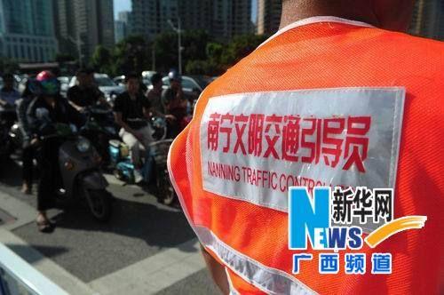 南宁一十字路口,文明交通引导员提醒市民不要闯红灯。