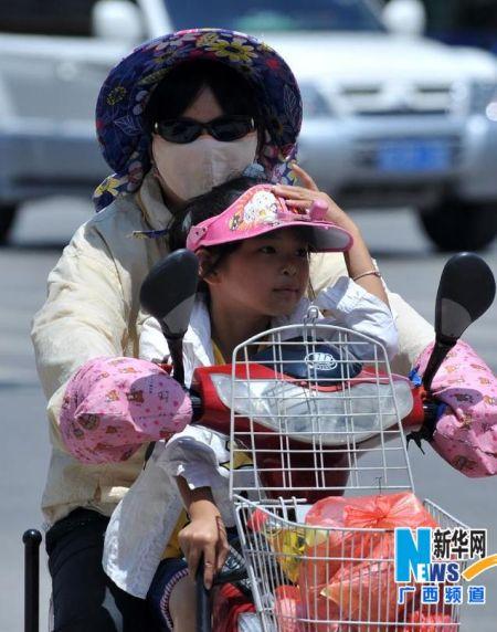 """7月6日,在广西南宁市民族大道,两名市民""""全副武装""""遮阳防晒。"""