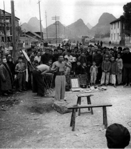 1944年,桂林百岁坊交叉口的街头卖艺人