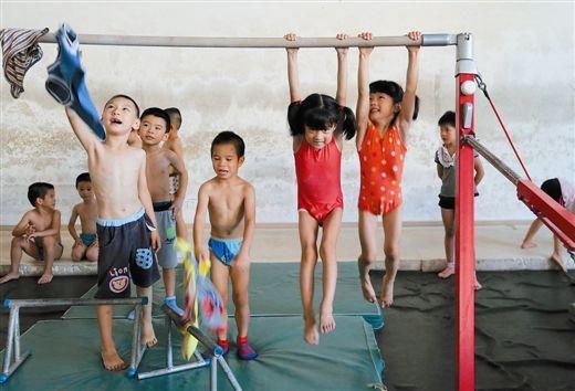小学员在高低杠上练习吊臂