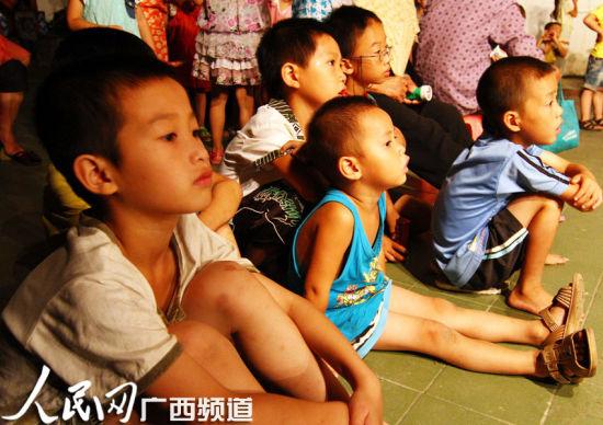 几名小朋友蹲坐在舞台边观看文艺演出
