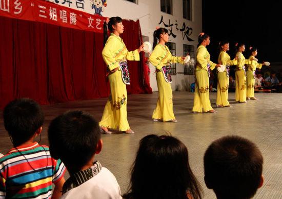 几名农村业余文艺队员正在舞台上表演快板说唱