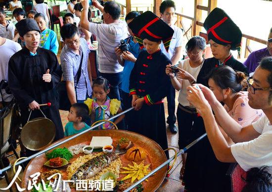 """游客们对直径1米盆装的""""壮家大盆菜""""非常感兴趣"""