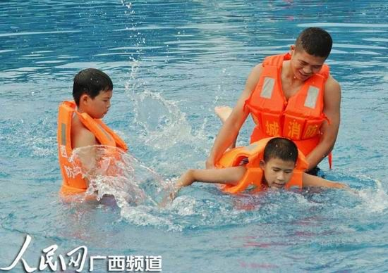 留守儿童跟消防官兵学习游泳