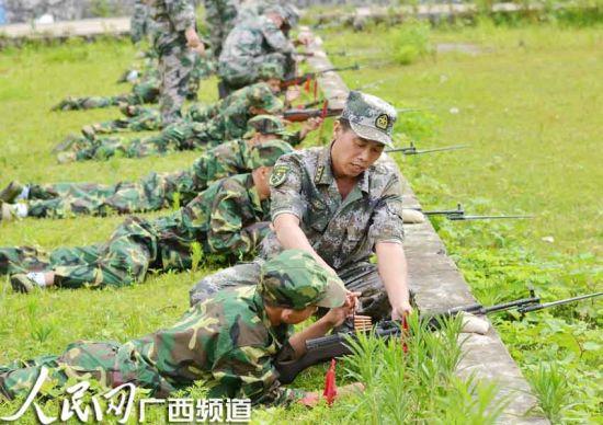 人武干部在指导一名90后的民兵进行装弹,准备实弹射击训练