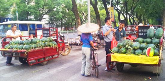 西瓜上市季节,这样占道卖瓜的情况很常见。