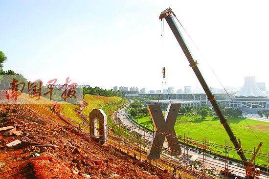 """会展路边坡施工现场,吊机正在将字母""""X""""吊起。南国早报记者 邹财麟摄"""