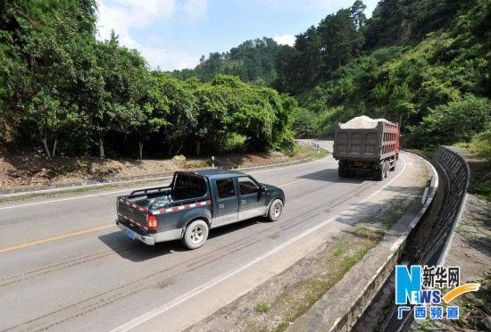 在国道S205线61公里至63公里路段上,两辆汽车进入一处弯道驰向环江县城