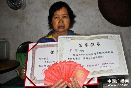 罗智的母亲捧着儿子20多本献血证和获奖证书(中广网发 陈君铭 摄)