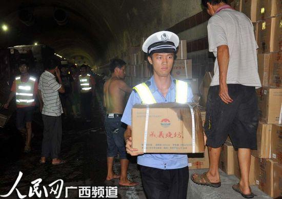 民警在倾洒的瓶装酒箱搬离货车,防止发生二次事故