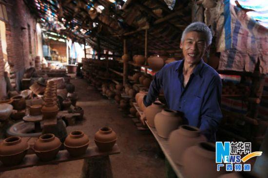 一名帮工将初步成型的陶器集中摆放阴干。
