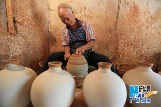 8月4日,颜福友师傅在广西宜州市郊区他的制陶作坊里给陶器制作装饰纹图。 4