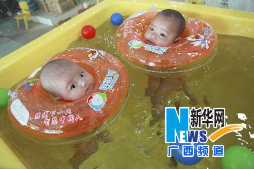 在广西全州县一家婴儿游泳馆,两名宝宝在游泳。