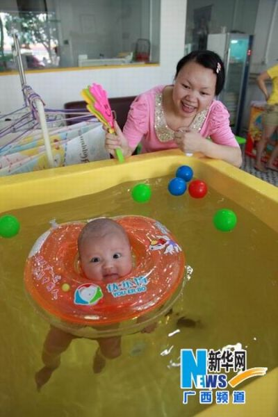一名母亲陪伴宝宝游泳。
