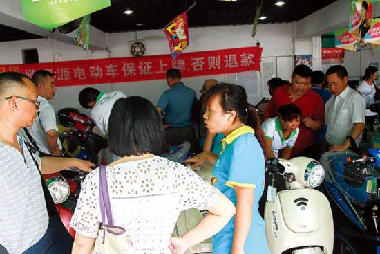 """南宁市中华路一电动车销售店内挂着""""电动车保证上牌,否则退款""""的横幅。"""