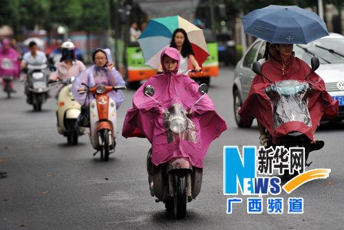 8月7日,在广西南宁市滨湖路,市民在雨中骑行。