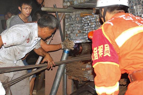 图为众人正在搬运钢材施救。