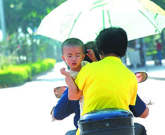 不少骑电动车出行的市民撑起了遮阳伞。南国早报记者 邹财麟摄