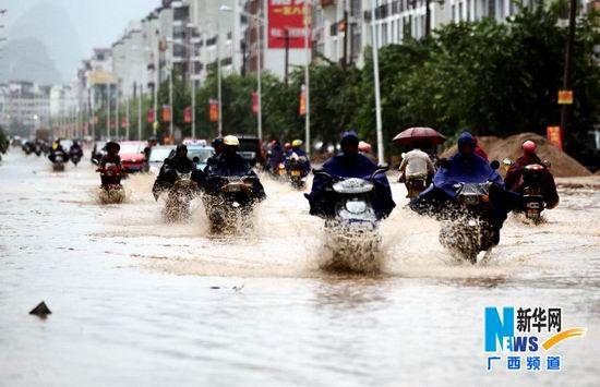 8月11日,在广西贺州市姑婆山大道,市民骑摩托车在积水中冒雨穿行。