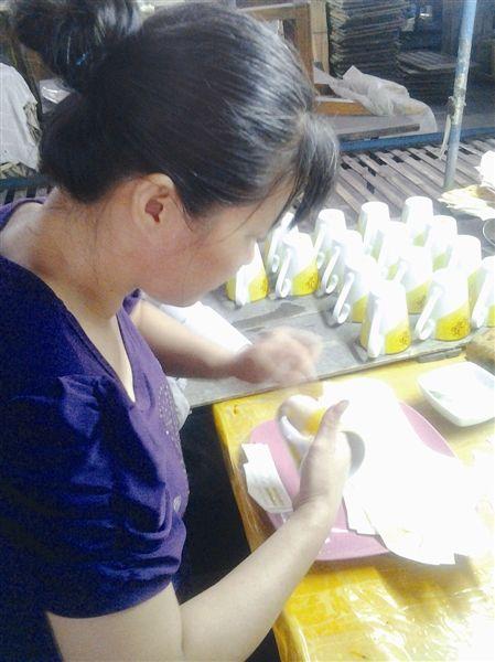 北流陶瓷企业工作人员正在给陶瓷杯身贴花。