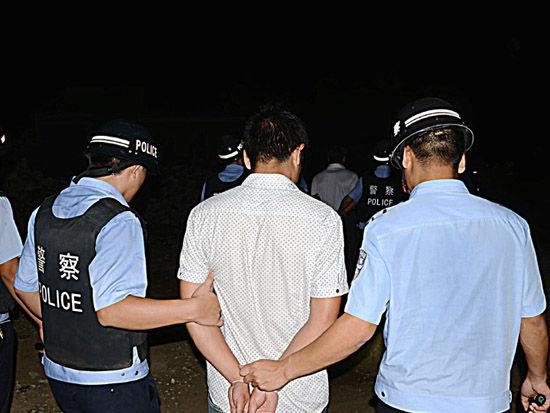 警方将行动中抓获的11名嫌疑人带离出村。人民网记者甘勇 摄