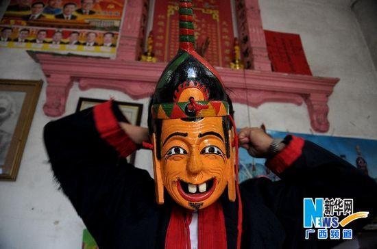 谭圣慈戴上面具准备为前来学习的小男孩演示傩面舞。