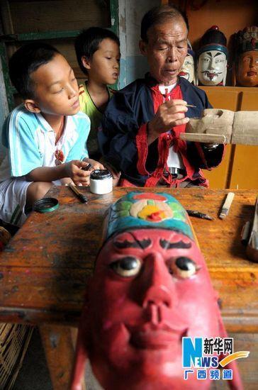 谭圣慈老人教前来学习的小男孩雕刻傩戏面具。