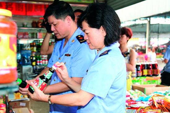 """执法人员在淡村市场对""""两会一节""""食品定点供应商进行检查。张鲁摄"""