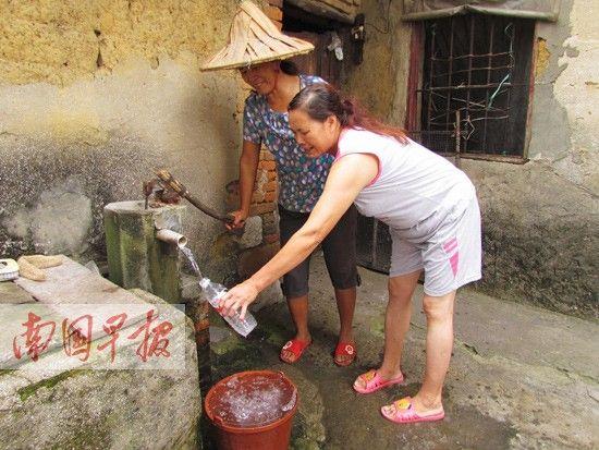 韦女士(右)家的井水变得像糖水一样甜。南国早报记者 周群能摄