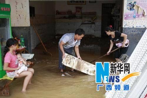 8月20日,来宾市象州县中平镇落沙村村民在清理淤泥。新华社记者 龚坚摄