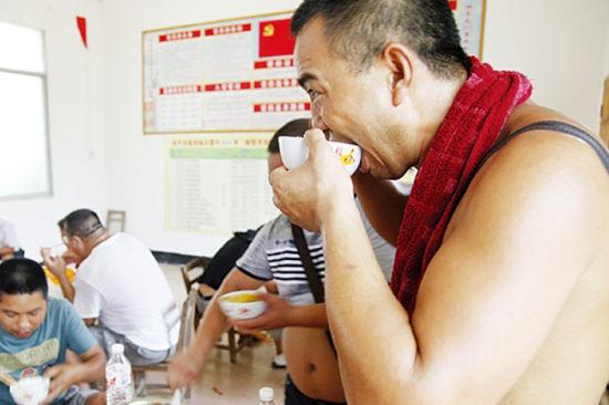 8月21日中午12时,在紫荆镇花蕾村的救助点,受困多日的司机能准点吃上米饭。