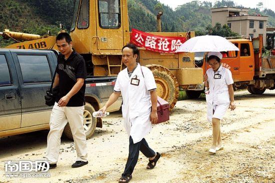 医务人员背着药箱,步行进入受堵路段为群众和司机看病。