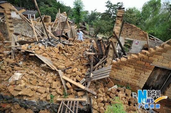 8月22日,贺州市富川瑶族自治县城北镇石狮村委周家村,一名村民在查看被洪水冲毁的房屋。新华社记者 陆波岸摄