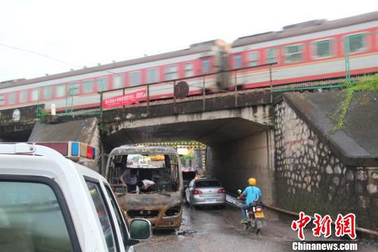 车辆大火被灭后,一辆火车从桥上经过。中新网记者林增崇 摄