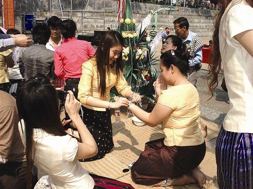泰国、老挝留学生在广西民族大学庆祝泼水节。图为老挝留学生正在进行拴线仪式。南国早报记者蒋晓梅 图