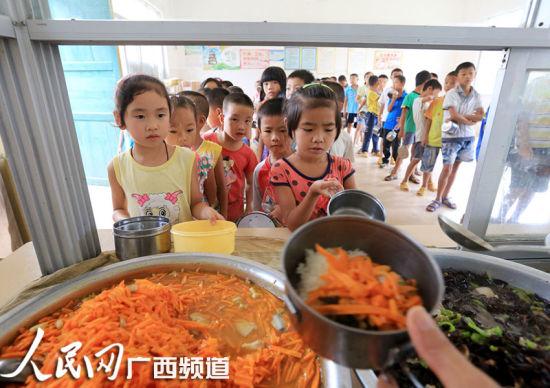融安县大坡乡岗伟村小学食堂,学生们在排队领取营养午餐。谭凯兴 摄