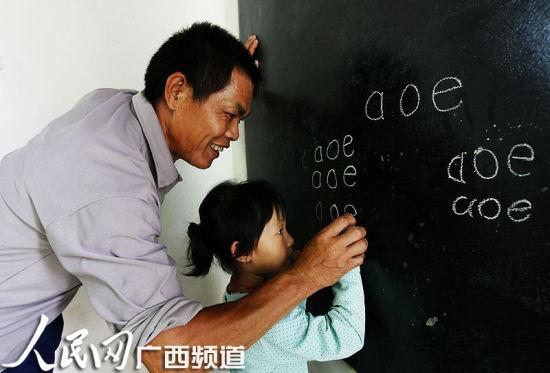 老师手把手教小朋友写拼音 人民网记者王勇摄