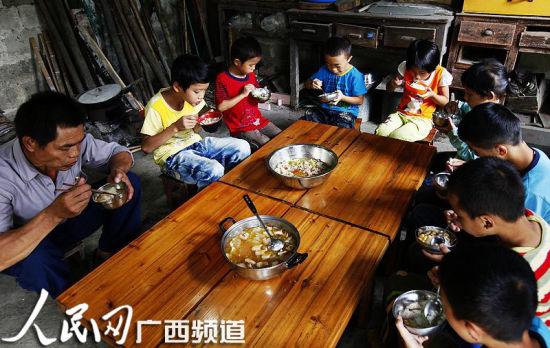 一群孩子和老师围坐在一块吃午饭 人民网记者王勇摄