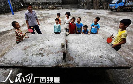 孩子们在操场上打乒乓球 人民网记者王勇摄