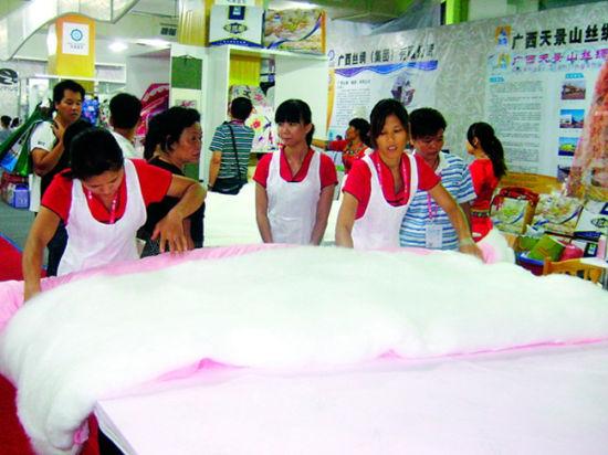 博览会农业展上,工人正在制作蚕丝被,吸引众多观众围观。 南国早报记者王春楠 摄