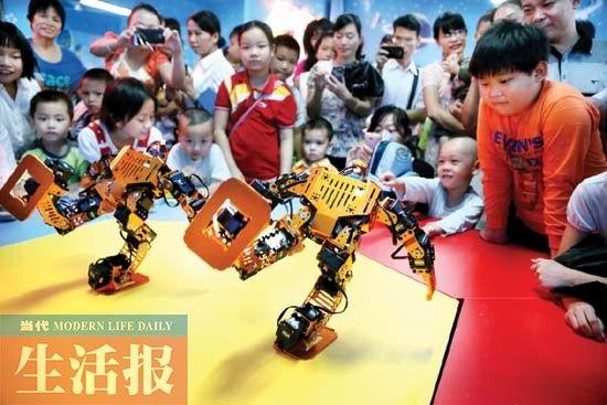 孩子们在看机器人表演跳舞。2