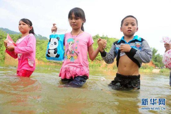 9月9日,在广西藤县古龙镇陈平村小学通往那龙组的桥上,放学回家的孩子们涉水通过桥面。