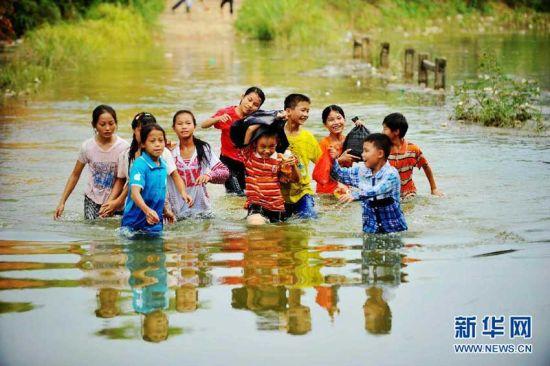 放学回家的孩子们涉水通过桥面。新华社记者张爱林 摄