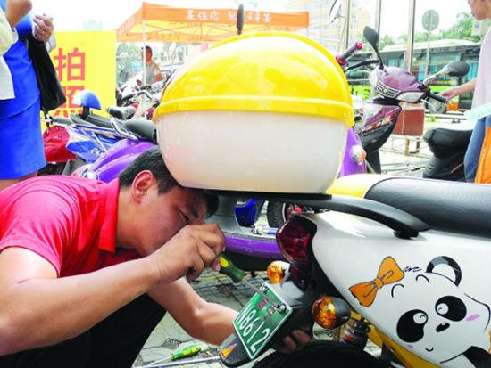 一名师傅在为车主安装车牌。南国早报记者程浩楠 实习生梁力文 图