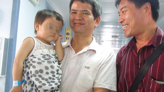 一名爱心人士(右)正好来医院探望贝贝。 南国早报记者谢奎 图
