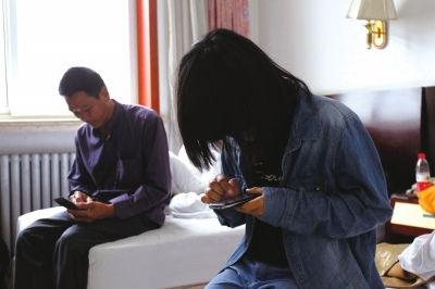 父女俩相顾无言,只能低头玩手机。京华时报记者谭青 摄