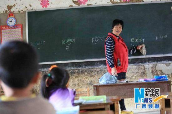 覃应英在给一年级学生上课,其他孩子在一起听课。新华社记者 覃刚 摄