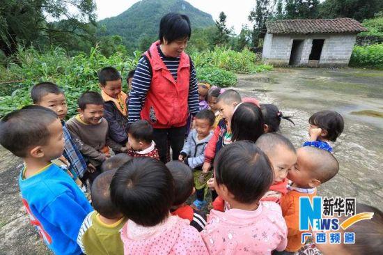 覃应英带着孩子们在教室外上自然课,启发孩子亲近和热爱大自然。新华社记者 覃刚 摄