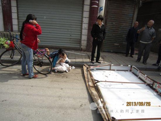 黎女士抱着孩子瘫坐在路边,王女士(红衣女子)在帮助她。(市民陈先生供图)